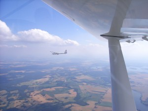 Das Vereinsflugzeug Puchacz fliegt neben der D-MORR Fk9. Sie fliegen nebeneinander.
