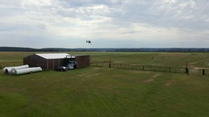 Zu sehen ist ein Hubschrauber der über dem Flugplatz schwebt und Polizisten an Seilen zu Boden lässt.