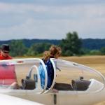 Eine Flugschülerin steigt in ein Segelflugzeug. Der Fluglehrer sitzt bereits im Segelflugzeug. Sie bereiten sich auf den Start an der Winde vor.