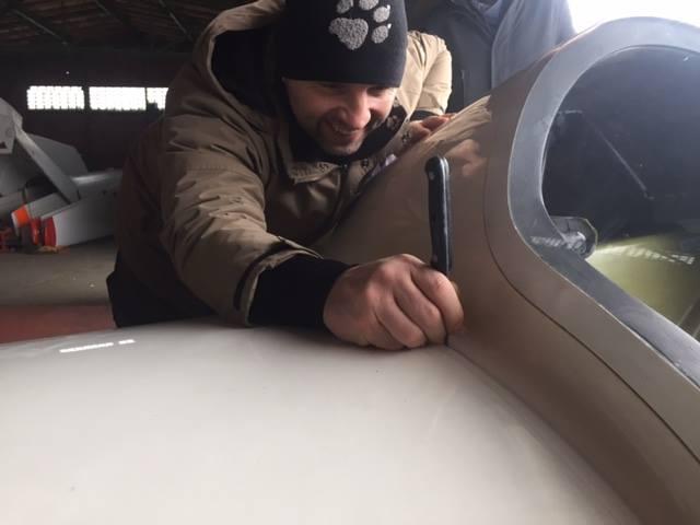 Mit einem Messer werden die abgeklebten Zwischenräumen zwischen dem Flugzeugrumpf und der Tragfläche durchrennt.